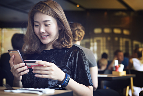 woman_in_cafe_with_credit_card_making_phone_purchase
